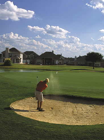 A man hits a golf ball from out of a sand trap at Blackhawk Golf Club in Pflugerville, Texas